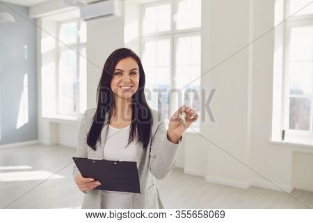 Realtor Agent Is A Realtor With Keys In Hand Against The Background Of A White Real Estate Room Apar