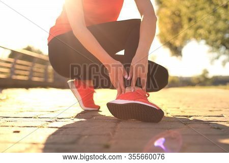 Sport Woman - Runner Holding Painful Sprained Ankle In Pain.