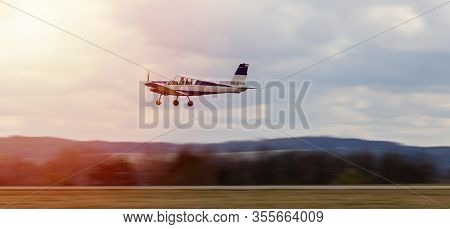 Ultralight Plane Take Off From Runway On Airports With Cloud Sky And Sun. Panning Photo