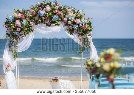 Wedding On The Beach. Wedding Arch Decorated Of Blue Material And Flowers On Tropical White Sand Bea