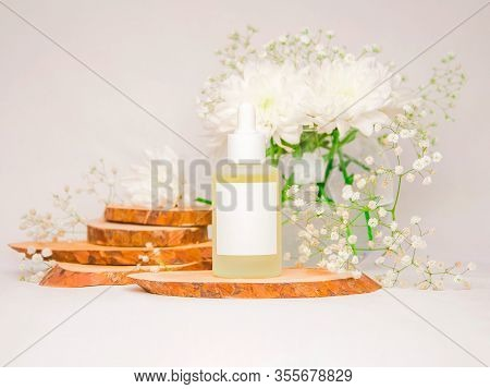 Glass Cosmetic Bottle With Pipette. White Background With Flowers And Wood Cuts. Moisturizing Cosmet