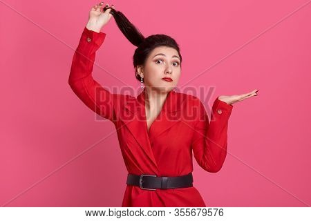 Horizontal Shot Of Surprised Beautiful Helpless Brunette Holding Her Ponytail, Having Shocked Facial