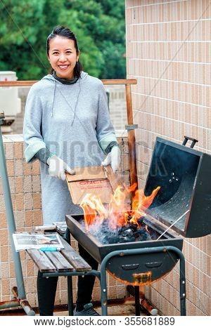 Hong Kong, China - January 17, 2016: Young Beautiful Smiling Asian Woman Kindles Fire On Barbecue. O