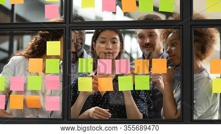Diverse Businesspeople Discussing, Planning Project On Sticky Papers Together