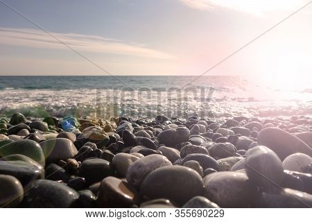 Sea Shore With Pebbles. Wet Sea Pebbles On The Beach And Quiet Sea Surf
