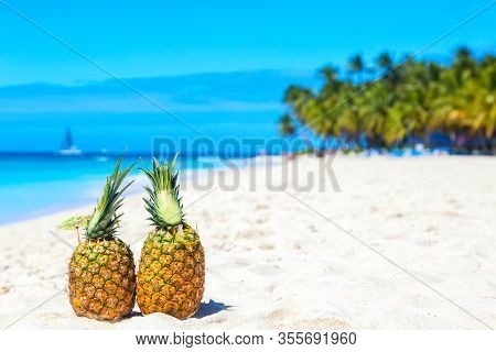 Tropical Pineapples Cocktails Pina Colada On Caribbean Beach With Palms And Ship. Saona Island, Domi