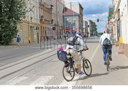 Lodz / Poland. 18 July 2019: Sports Family Moving Around City On Bicycle Rides. Family With Child Ri