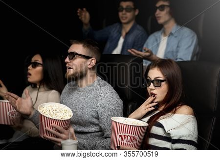Showtime Concept. Shocked Young People In 3d Glasses Watching Interesting Movie In Cinema