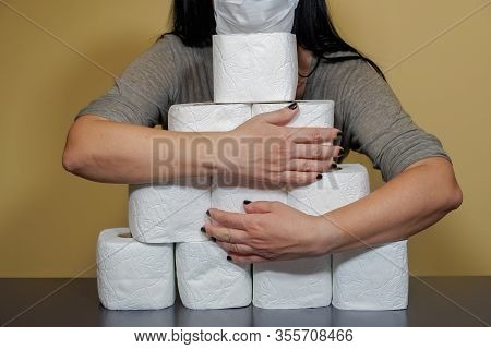Toilet Paper Shortage Concept With Female Holding Stacked Rolls. A Woman Covers With Her Hands A Pil