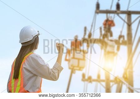 Successful Female Electrical Engineers Stood At The Workplace Against The Sunrise Background.