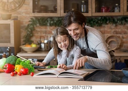 Happy Dad And Little Daughter Checking Recipe In Cookbook At Kitchen Together While Cooking Healthy