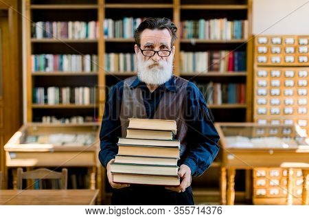 Portrait Of Attractive Bearded Old Man Wearing Shirt And Leather Vest, High School Teacher Or Librar