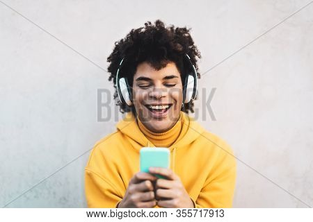 Happy Afro Man Using Mobile Smartphone Outdoor - Young Guy Having Fun Listening Music With Wireless