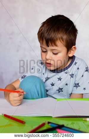 Little Boy Drawing With Color Pencils. Boy, Drawing A Picture For Fathers Day. Small Boy Draws At Th
