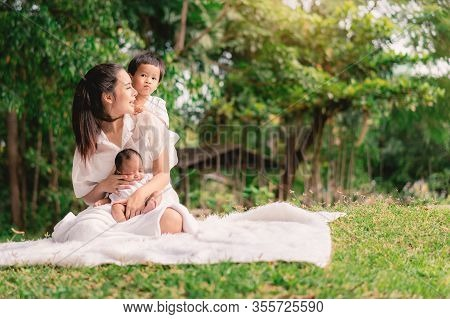 Happy Loving Family. Asian Young Beautiful Mother And Her Children, New Born Baby Girl And A Boy Sit