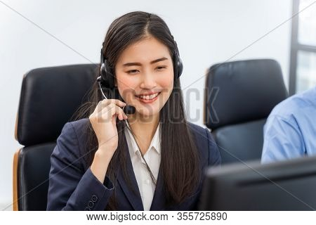 Happy Smiling Operator Asian Woman Customer Service Agent With Headsets Working On Computer In A Cal