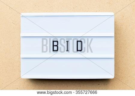White Lightbox With Word Bid On Wood Background