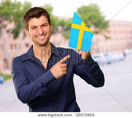 Portrait of a man holding flag, outdoor