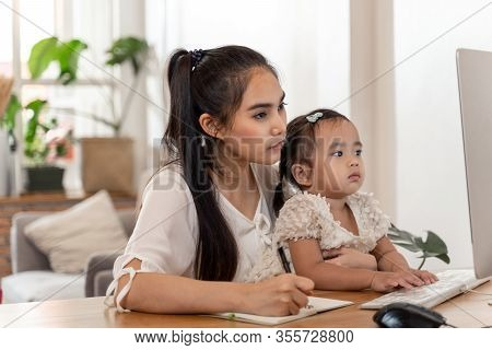 Asian Young Mother Working From Home And Holding Baby While Talking On Phone And Using Computer Whil