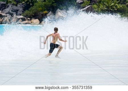 Young Teenager Boy Enjoys Summer Holiday In Sea. The Kid Runs Away From Huge Wave.