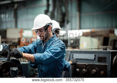 Men Industrial Engineer Wearing A White Helmet While Standing In A Heavy Industrial Factory Behind.