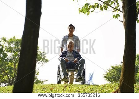 Young Asian Adult Son And Wheelchair Bound Father Enjoying Nature In Park