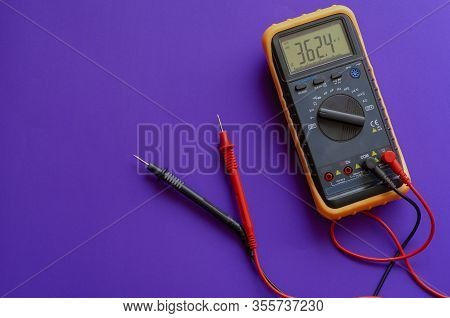 Multimeter On A Lilac Background. Yellow Multimeter, A Multimeter Or A Multitester Is An Electronic
