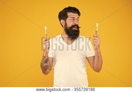 Teeth Hygiene. Ultrasonic Teeth Cleaning Technology. Bearded Man Holds Toothbrushes Yellow Backgroun