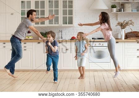 Overjoyed Parents Have Fun Dancing With Small Kids