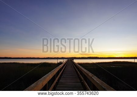 A Long Dock Leads Out To A Marsh And River At Sunset In South Carolina; Copy Space