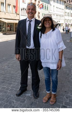 Happy Couple Standing Arm In Arm In The Street Of Old Town Brugg And Looking To Camera On The 4th Of