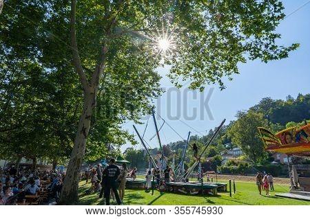 Relaxing Adults Under The Trees Of Schützenmatt Brugg While Children Having Fun At Funfair And Jump