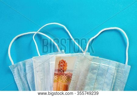 Three Medical Masks And Bank Note Of 5000 Rubles On Blue Background. Concept Of Growth Price Of Face