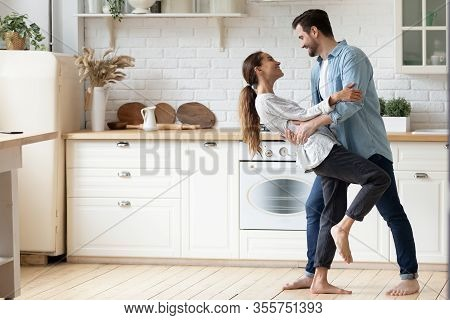 Happy Loving Couple Dancing Romantic Dance On Date In Kitchen