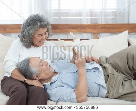 Senior Elder Asian Man Lie Down On Sofa Read Book With Grandmother In Living Room At Home.