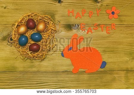 Happy Easter Message With Painted Eggs In Straw,bunny And Flower On Wooden Table