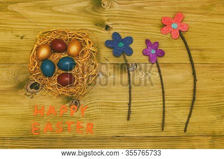 Painted Easter Eggs In Straw With Flowers On Wooden Table.