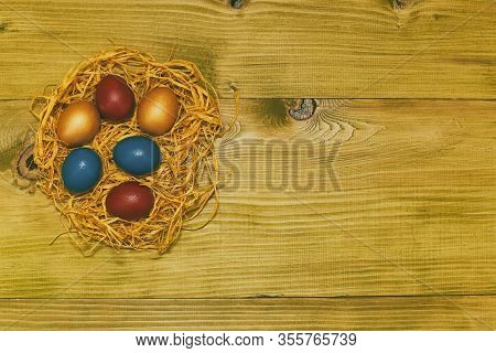 Painted Easter Eggs In A Straw On Wooden Table