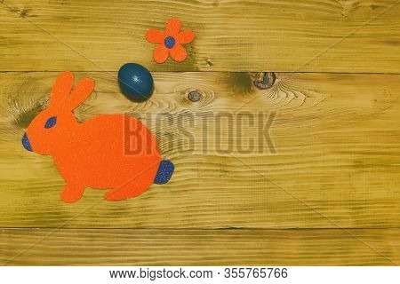 Painted Easter Egg With Paper Bunny And Flower On Wooden Table.