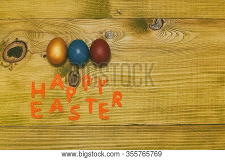 Happy Easter Message With Painted Eggs On Wooden Table.
