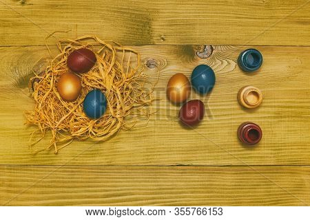 Painted Easter Eggs In Straw And Colors For Painting On Wooden Table