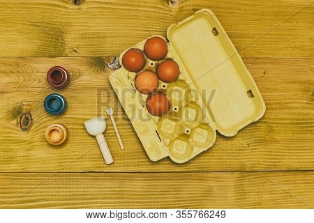 Eggs In A Box And Colors For Painting On Wooden Table.