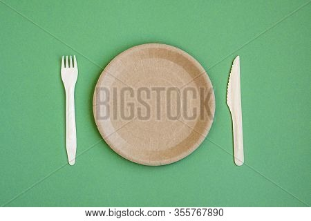 Eco- Friendly Tableware For Food And Wooden Eco-knife, Fork, Spoon On A Green Background With A Copy