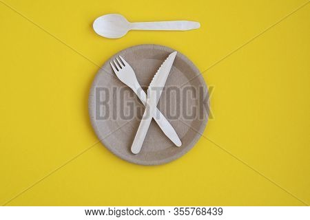 Eco- Friendly Tableware For Food And Wooden Eco-knife, Fork, Spoon On A Yellow Background With A Cop