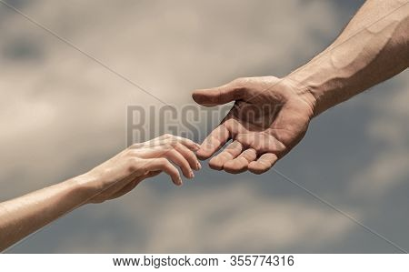 Hands Of Man And Woman On Blue Sky Background. Lending A Helping Hand. Giving A Helping Hand. Solida