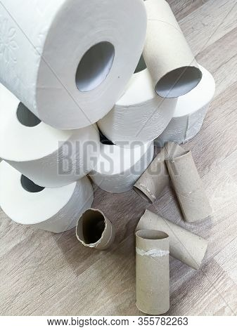 Empty and full white toilet paper rolls stacked
