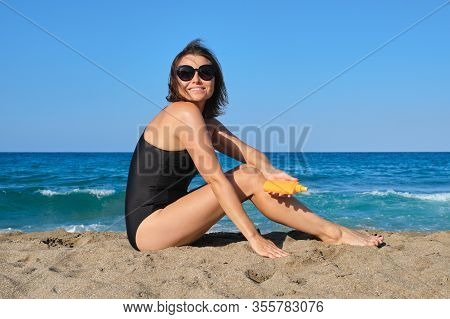 Mature Beautiful Woman Sitting On Beach Using Sun Protection Cream, Care Beauty And Health Of Middle