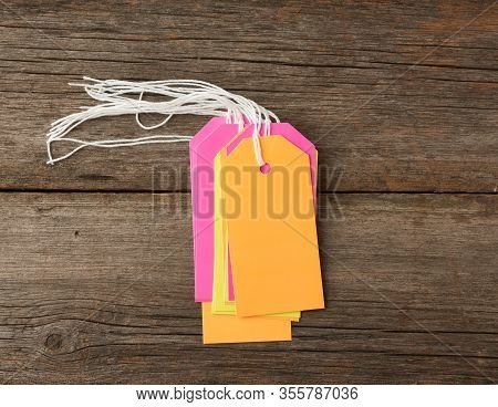 Stack Empty Color Paper Tags Tied With White String. Price Tag, Gift Tag, Sale Tag On A Gray Wooden