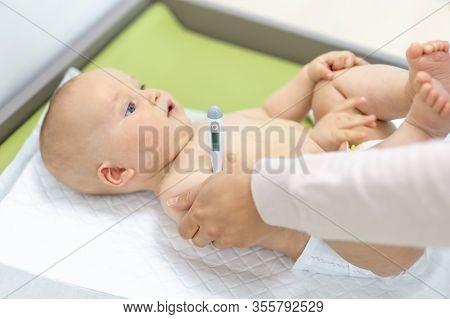 Doctor Pediatrist Examining Child. Pediatrician Taking Baby Temerature At Office. Medicine, Healthca