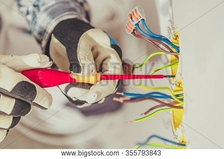 Residential Electricity System. Professional Electrician Preparing Electric Wall Outlet Inside A Hou